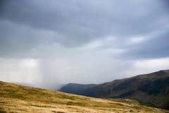 Paesaggio mistico con le nuvole di pioggia alte nelle montagne Immagini Stock