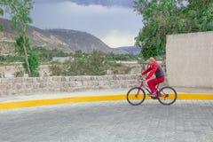Paesaggio, montagne e natura La strada è posta con una pietra e un uomo la guida su una bicicletta, azionamenti lungo la strada immagine stock libera da diritti