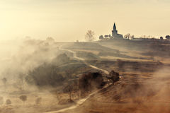 Paesaggio nebbioso del paese con la chiesa Fotografia Stock Libera da Diritti