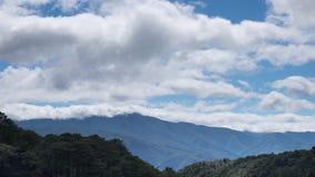 Paesaggio nebbioso di mattina con le nuvole commoventi a cielo blu sopra la foresta e la montagna video d archivio