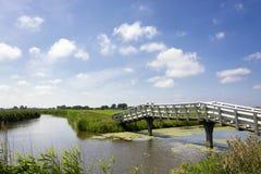 Paesaggio olandese tipico con i prati, l'erba, il ponte, acqua, cielo blu e le nuvole verdi fotografie stock libere da diritti