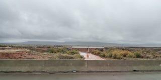 Paesaggio orientale del New Mexico con il ponte, fiume fangoso rosso immagine stock