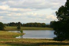 Paesaggio pastorale con il lago Fotografie Stock
