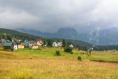 Paesaggio pittoresco del villaggio su un fondo delle montagne immagini stock