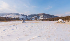 Paesaggio rurale con i campi ed i mucchi di fieno innevati, nell'inverno Fotografie Stock Libere da Diritti