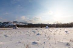 Paesaggio rurale con i campi ed i mucchi di fieno innevati, nell'inverno Fotografie Stock