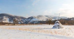 Paesaggio rurale con i campi ed i mucchi di fieno innevati, nell'inverno Fotografia Stock