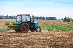 Paesaggio rurale con il vecchio trattore in un seme della scrofa del campo Immagine Stock