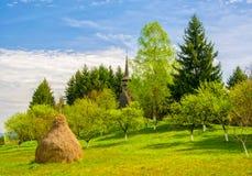 Paesaggio rurale della molla scenica con i maramures tradizionali chiesa neogotica, Maramures, Romania Immagini Stock Libere da Diritti