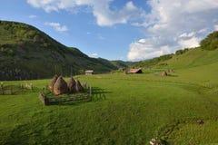 Paesaggio rurale della montagna con i mucchi di fieno contro il cielo nuvoloso Fotografia Stock
