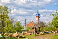 Paesaggio rurale della primavera con la chiesa neogotica di maramures tradizionali nel villaggio di Sapanta, Romania Fotografie Stock Libere da Diritti