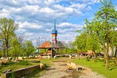 Paesaggio rurale della primavera con la chiesa neogotica di maramures tradizionali nel villaggio di Sapanta, Romania Immagini Stock Libere da Diritti