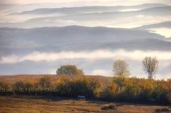 Paesaggio rurale di autunno con nebbia fotografie stock