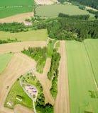 Paesaggio rurale di estate con i hauses sul campo di erba verde e sulle nuvole piovose Immagini Stock Libere da Diritti