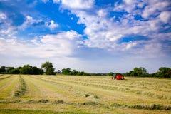 Paesaggio rurale di estate con il trattore che raccoglie fieno nel campo Immagine Stock