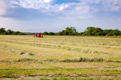 Paesaggio rurale di estate con il trattore che raccoglie fieno nel campo Fotografia Stock