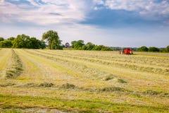 Paesaggio rurale di estate con il trattore che raccoglie fieno nel campo Immagini Stock Libere da Diritti