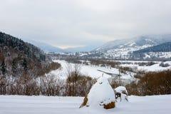 Paesaggio rurale di inverno al piede delle alte montagne Immagine Stock
