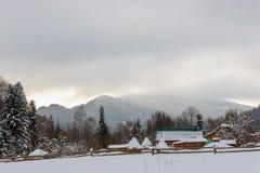 Paesaggio rurale di inverno al piede delle alte montagne Immagini Stock