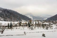 Paesaggio rurale di inverno al piede delle alte montagne Fotografia Stock