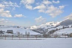 Paesaggio rurale invernale della montagna nelle valli delle montagne di Bucegi nel villaggio di Magura fotografia stock