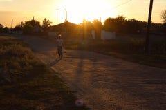Paesaggio rurale: la siluetta di un ragazzo su una bicicletta nel tramonto Immagine Stock