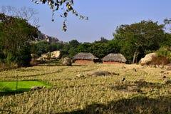 Paesaggio rurale tradizionale indiano con due casette con il tetto ricoperto di paglia fotografie stock
