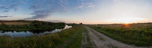 Paesaggio rurale, tramonto La strada allunga nella distanza, il fiume dalla parte di sinistra Immagini Stock Libere da Diritti