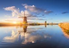 Paesaggio rustico con i mulini a vento olandesi stupefacenti ad alba Fotografia Stock