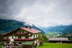 Paesaggio scenico con le costruzioni tradizionali in villaggio in alpi Fotografie Stock