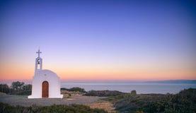 Paesaggio scenico con una chiesa e un mar Egeo bianchi al tramonto immagini stock