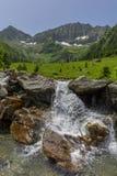 Paesaggio scenico della montagna nevosa nei precedenti e di piccola cascata nella priorità alta Fotografia Stock Libera da Diritti