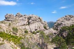 Paesaggio selvaggio della montagna, rocce sotto cielo blu Fotografie Stock