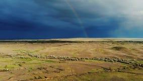 Paesaggio soleggiato di estate sul campo davanti ad un temporale nella sera un arcobaleno compare vista da un occhio del ` s dell stock footage
