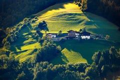 Paesaggio soleggiato favoloso con i prati verdi, gli alberi e le costruzioni tipiche delle alpi Immagine Stock