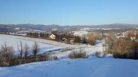 Paesaggio soleggiato in villaggio con neve Fotografia Stock