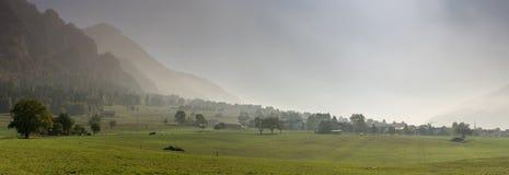 Paesaggio svizzero rurale della campagna con i campi dell'azienda agricola e le montagne nebbiose e foresta in autunno tardo fotografie stock