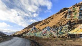 Paesaggio tibetano in Cina con le bandiere di preghiera su priorità alta e su una strada dalla parte di sinistra Fotografia Stock