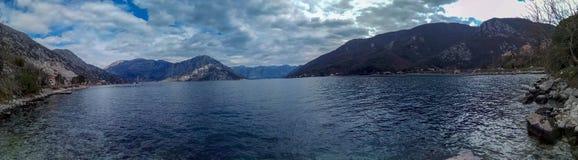 Paesaggio in tonalità differenti del blu: montagne e le loro riflessioni nell'acqua calma del mare adriatico fotografia stock libera da diritti