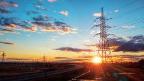 Paesaggio: Torre elettrica ad alta tensione sul fondo, sulla strada, sul cielo blu e sulle nuvole di tramonto Fotografia Stock