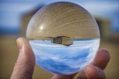 Paesaggio tropicale dell'isola, casa sola alla spiaggia Sparato attraverso la palla di vetro Fotografia Stock