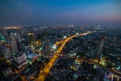 Paesaggio urbano asiatico moderno della megalopoli alla notte Bangkok, Tailandia fotografie stock