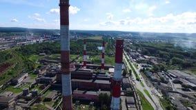 Paesaggio urbano con la pianta di fabbricato industriale con tre tubi industriali rossi e bianchi alti sopra chiaro cielo blu sen video d archivio