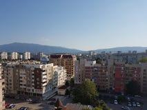 Paesaggio urbano con una montagna nei precedenti Fotografia Stock