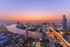 Paesaggio urbano del fiume nella città di Bangkok con la costruzione dell'alta carica nella notte Fotografia Stock