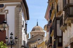Paesaggio urbano della chiesa spagnola attraverso le costruzioni fotografia stock libera da diritti