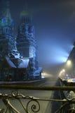 Città nebbiosa romantica di inverno di notte con una cattedrale e un canale congelato Immagini Stock
