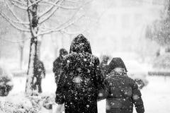 Paesaggio urbano di nevicata con la gente che passa vicino Fotografia Stock Libera da Diritti
