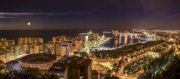Paesaggio urbano di notte della città di Malaga con il mar Mediterraneo e del porto nei precedenti Fotografia Stock Libera da Diritti