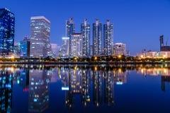 Paesaggio urbano di notte di Bangkok attraverso il lago urbano Immagine Stock Libera da Diritti
